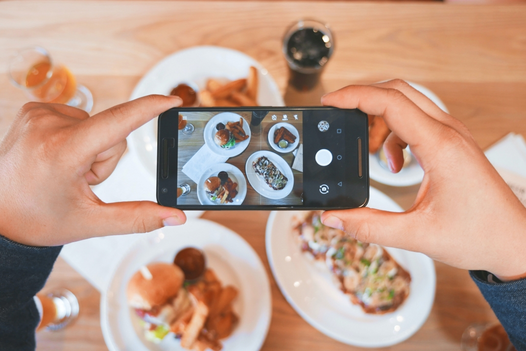 person taking photo of food on phone