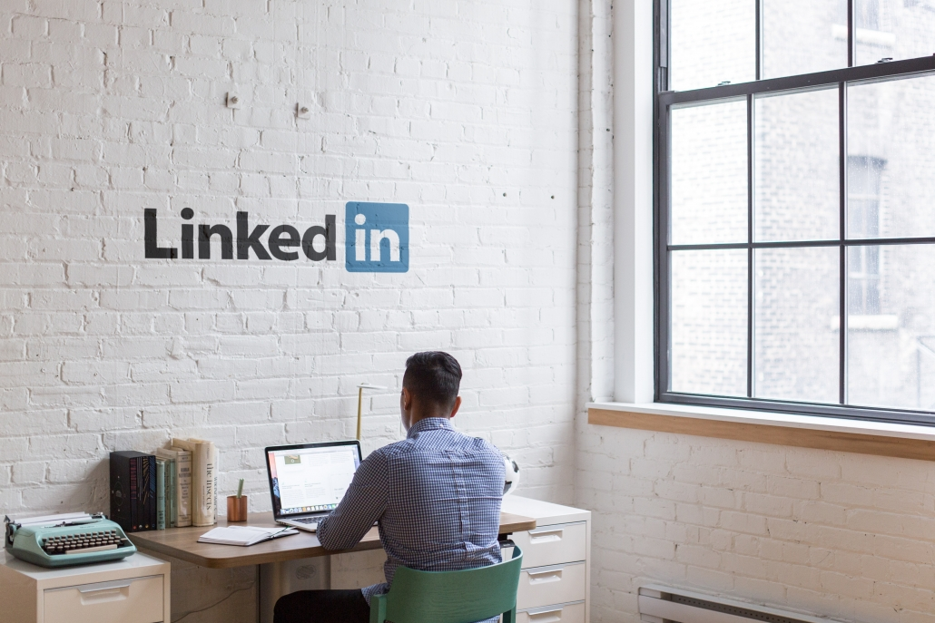 Man on laptop with LinkedIn logo on wall