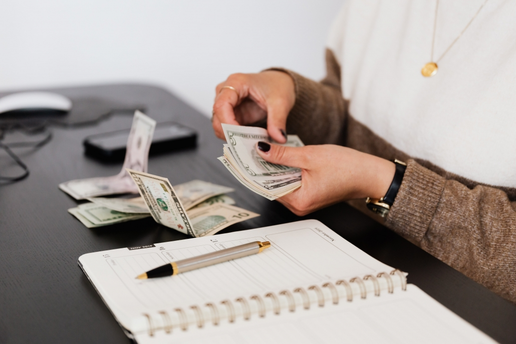 person counting money on a desk