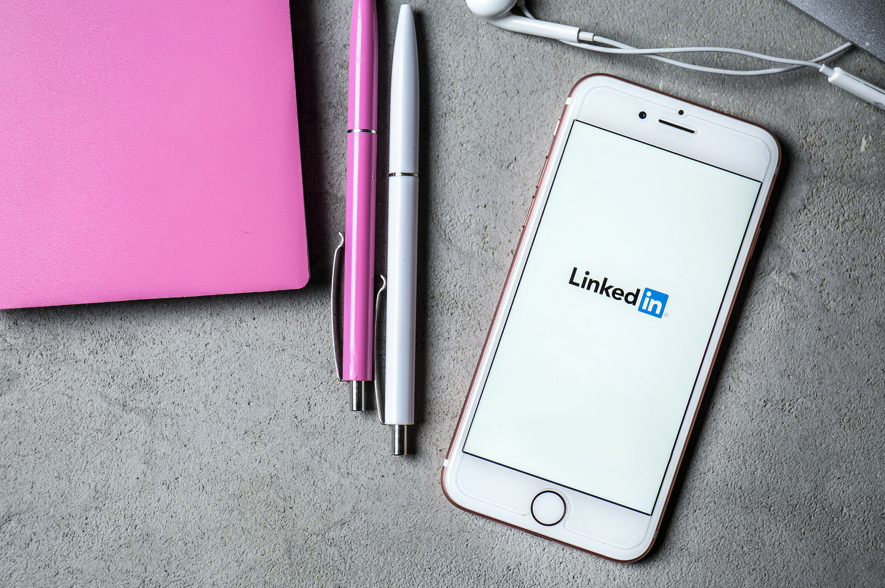 LinkedIn on mobile next to pens and book